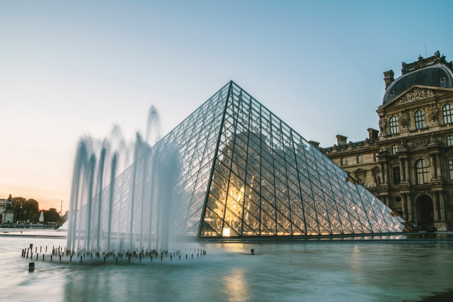 Louvre Pyramid at night with fountains in foreground