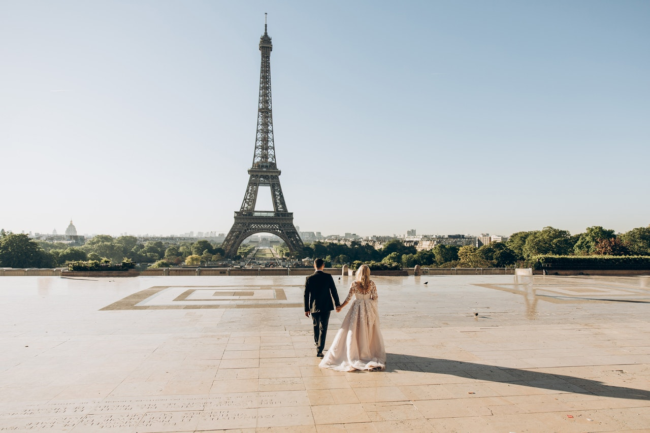 Couple holding hands at the Eiffel Tower