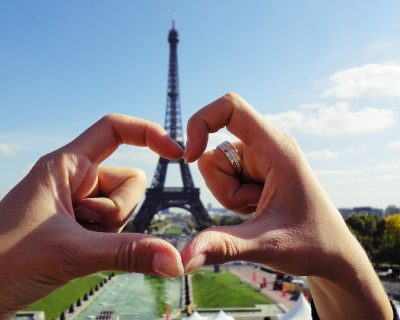 Heart shaped hands around the Eiffel Tower in Paris