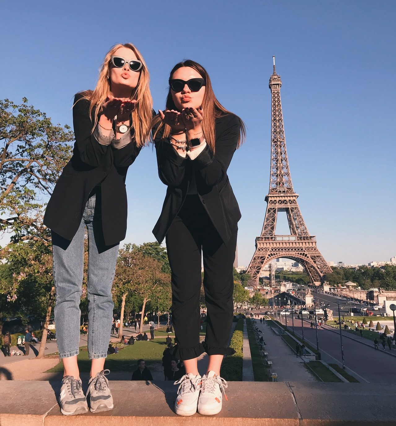 Women blowing kissed in front of the Eiffel Tower for a photo
